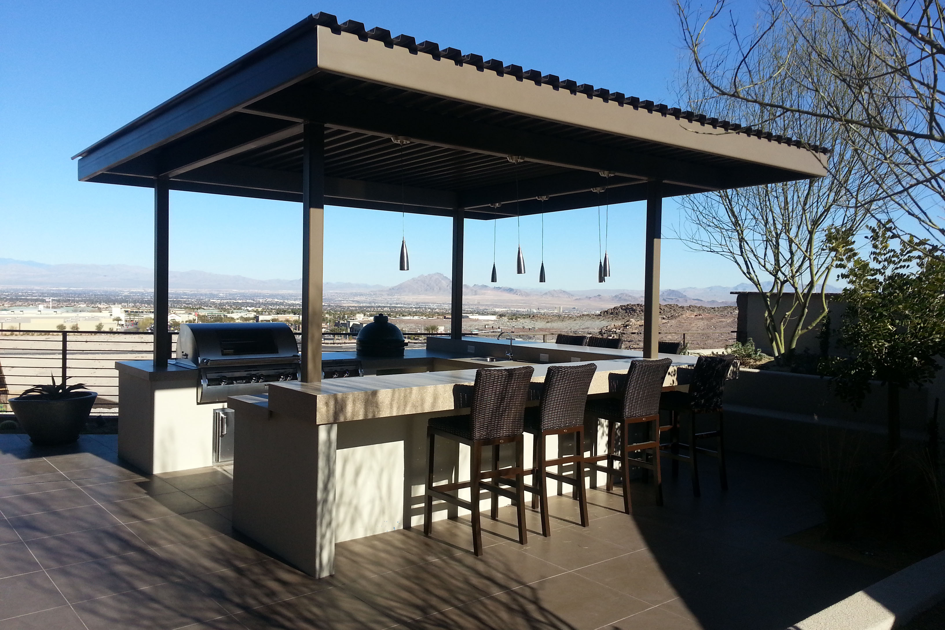 freestanding covered outdoor kitchen with BBQ, smoker and sinks, pendant lighting and seating for 8, overlooking Las Vegas