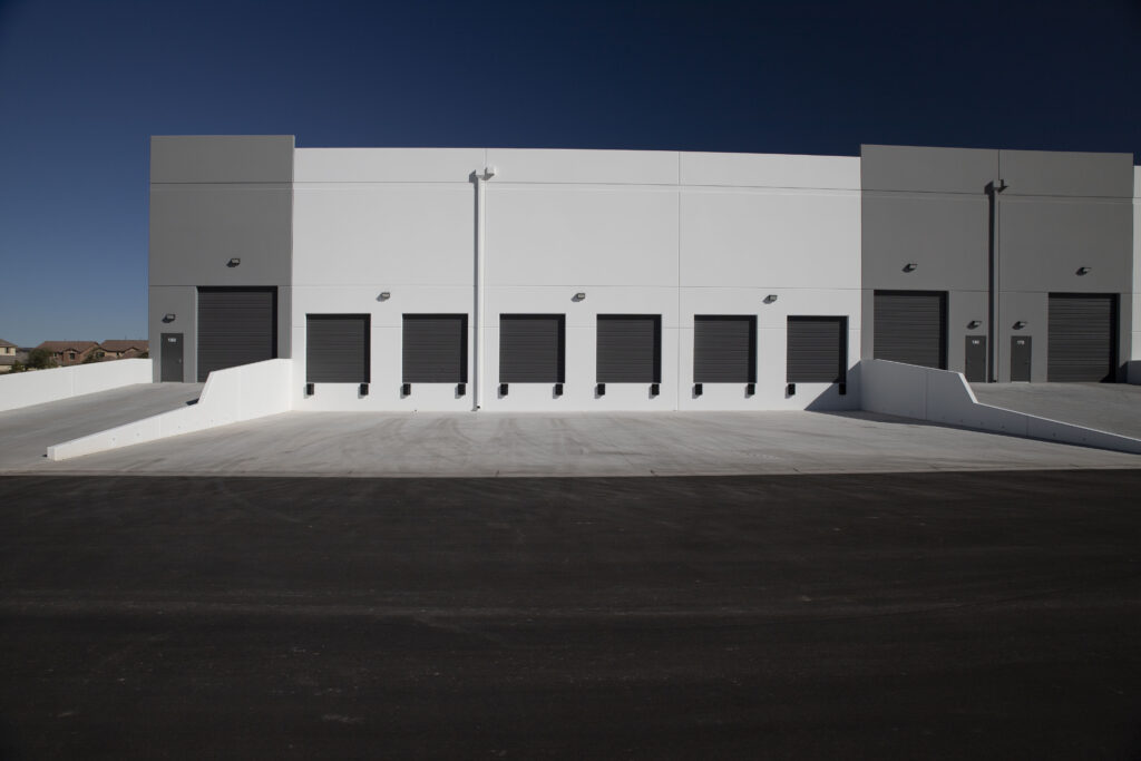 A commercial loading bay with 6 doors in the center and 2 larger doors flanking them.