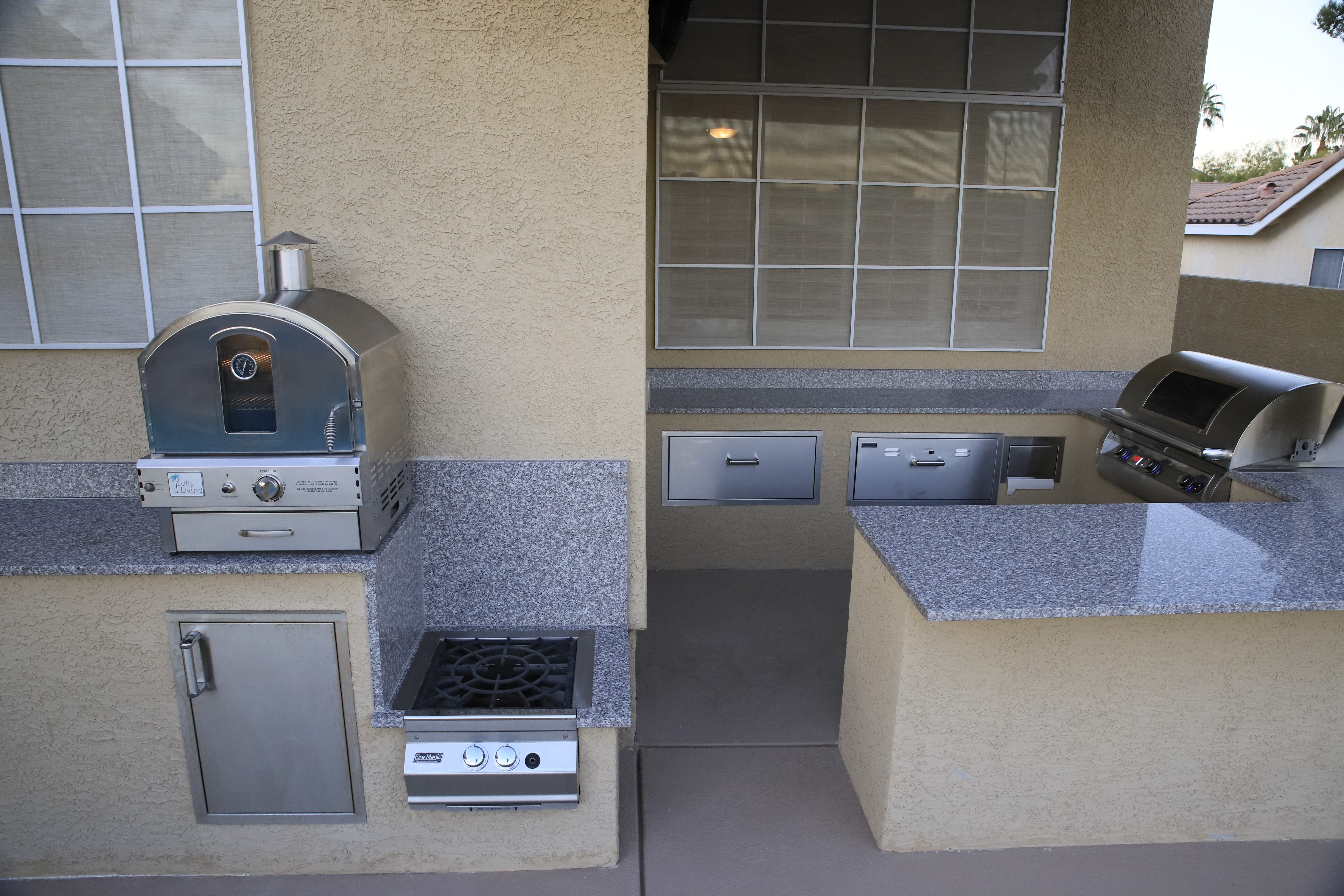 beautiful and simple outdoor kitchen with a stainless steel pizza oven, low burner, BBQ, warmer, and even a covered paper towel holder